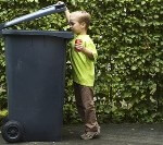 Boy putting rubbish in a bin